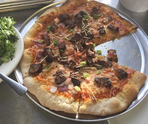 Thin crust pizza with Steak, Scallions and Cheddar.   By City Farm Events Boston.